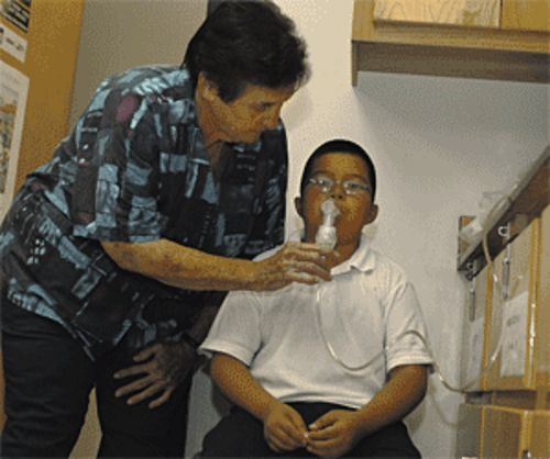 Mary Chick, head nurse for the Roosevelt Elementary School District, administers a breathing treatment.
