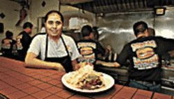 Mountain of meat: Co-owner Enrique De La Torre with his restaurant&#039;s signature &quot;La Presa&quot; torta.