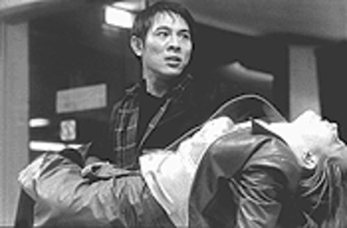 Liu Jiuan (Jet LI) carries a shaken Jessica (Bridget  Fonda) to safety in Kiss of the Dragon.