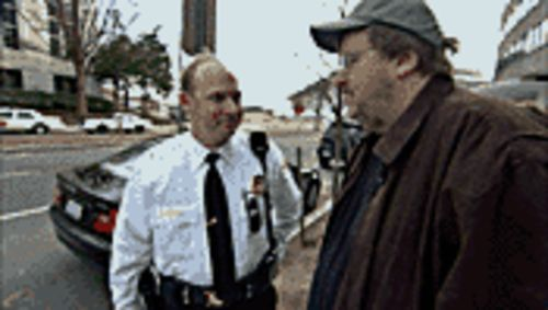 Bushwhacking: Michael Moore (right) is stopped by a Secret Service agent outside the Saudi embassy in Fahrenheit 9/11.