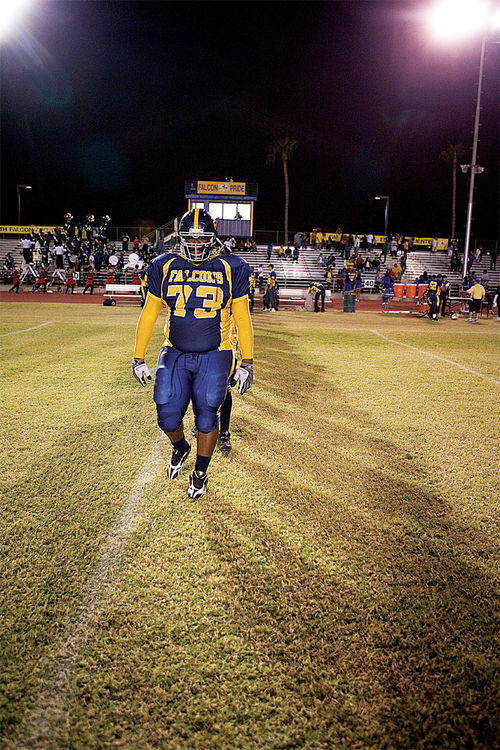Co-captain Tre Fields leads the Carl Hayden Falcons onto the field before a recent game at the Phoenix school.