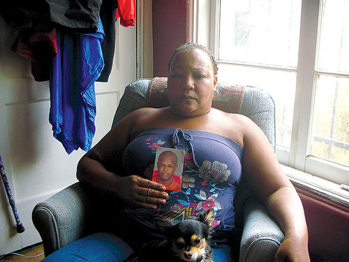 Kini Seawright, in Peggy Plews' apartment with a photo of her late son, Dana.