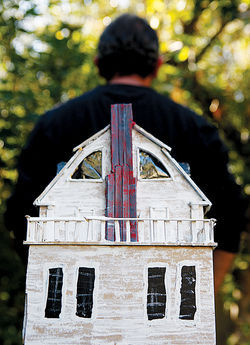 The iconic face-like Amityville house (seen here as a model built by a friend of Quaratino's) has added to the tale's mystique.