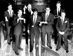 Romney (center left) and a colleague hold a bill together in a Bain Capital photo.