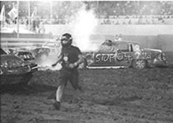 Drivers run from the arena as fire breaks out.