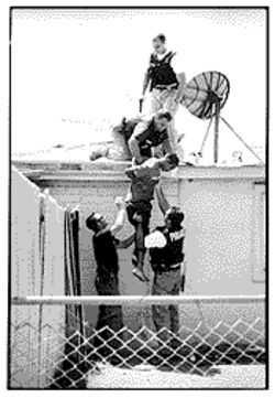 "The SAU frequently picks up people wanted by other police units. Here, SAU officers Dave Haas,  top, Rich Shore and Bob Knapp, bottom right, nab a probation violator who tried to flee by climbing up on his roof.  At bottom left is a patrol officer who spent the day with SAU, ""test-driving"" the squad."
