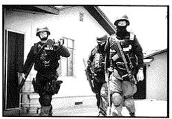 Officers returning from a search warrant carry the main tools used by the SAU: a heavy battering ram, a large steel pry bar and a shield to protect the entry team against gunfire.