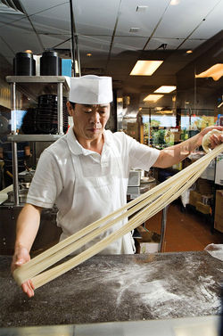 Chef Zhang Qiang prepares the house specialty — hand-pulled noodles — at China Magic Noodle House.