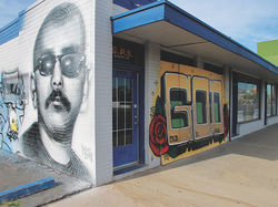 16th Street&#039;s new Por Vida Gallery, with a mural by El Mac