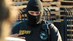 An MCSO deputy in a ski mask at an immigration sweep.