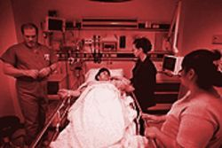 Lucy Alday, an interpreter at Good Samaritan, stands at the bedside of a patient to help the woman and her mother understand what is happening and to interpret for the doctor.