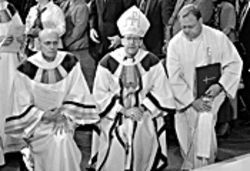 Fushek (right) kneels beside new Bishop Thomas  Olmsted at Olmsted's installation as leader of the  Phoenix Diocese in December 2003. Olmsted later  demoted Fushek.