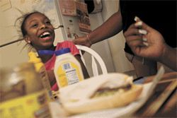 "Greiana Marchand, 9, laughs as her aunt Kazanda Millon prepares a ""po' boy"" in Nelda Millon's kitchen in Glendale."