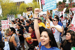 DREAMer Daniela Cruz, fist raised, during a recent march; Cruz is both hopeful and skeptical of President Obama&#039;s June 15 promise not to deport DREAMers.