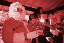 Santa tries to cheer one of the several hundred children who attended the annual Milpas Christmas party.
