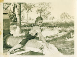 A young Joyce Farmer plays on the irrigation pipe that supplied water to her grandparents' Goodyear cotton ranch in the 1940s.