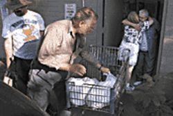 AGAPE network volunteers Lloyde Malone (center) and Tommy Tharp (left) load Malone's cart with groceries while AGAPE's Bonnie Heare (far right) gets a hug from volunteer Patricia Glover.