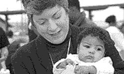 Governor Janet Napolitano poses with an unidentified child at a Martin Luther King Day event. She wants to create a model child welfare system.