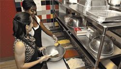 Creating a stir: Erika Crepinsek (left) and Krystal Nelson from Entrees Made Easy whip up a batch of shepherd's pie.