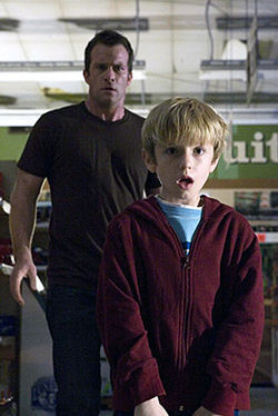 In a drugstore, no one can hear you scream: Thomas Jane and Nathan Gamble face the mist monsters.