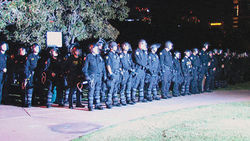 A wall of Phoenix police officers forms at Margaret T. Hance Park to remove a few dozen Occupy Phoenix protesters who remained at the park hours after it had closed.