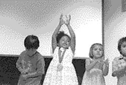 Cambria Gates, then aged 3, raises her hands as she sings during her preschool graduation ceremony last year. On her neck is a medal she earned for reading more than 100 books.