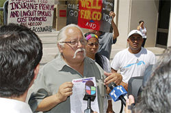 "Salvador Reza in front of the Wells Fargo building, with his ""eviction notice"" for Sheriff Joe."