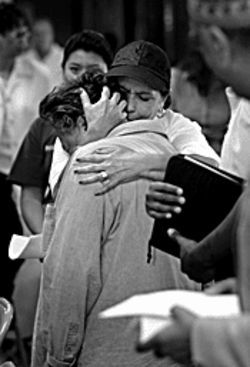 A Red Cross volunteer embraces a Katrina evacuee.