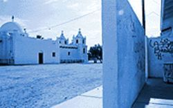 Sacred ground: A wall protecting Guadalupe's Yaqui temple (right) is defaced by gang graffiti. The Catholic church is in the background.