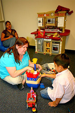 Speech therapist Joanne McIntyre works with 5-year-old Javier Acosta while his mother, Thelma, looks on.