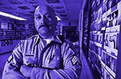 Sergeant F. Duran, in a prison area where the walls are lined with photos of documented gang members.