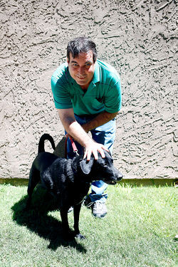 Shelton with Queenie, a black Lab 
