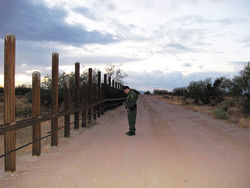 U.S. Border Patrol Agent Eric Cantu stands at the U.S.-Mexico border, marked here by a fence of steel poles to keep out cars.
