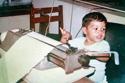 Family photo of Miguel Angel Lopez Solana, about 2 years old, sitting at the Telex machine in his father's office at Notiver.