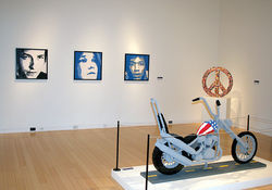 Captain America (foreground) and a triptych of Bob Dylan, Janis Joplin, and Jimi Hendrix.
