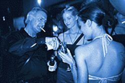 Essence Entertainment owner John Lemonis parties with two of his escorts.