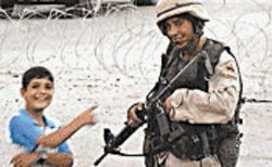 An American soldier spends some down time with an Iraqi boy in Gunner Palace.