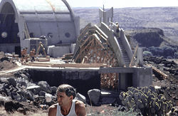 Soleri, circa 1973, with Arcosanti's completed north vault in the background and early stages of ceramics apse construction.