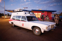 Arizona Ghostbusters suit up beside  their version of the Ecto-1 car.