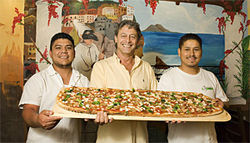 Pizza A Metro owner Maurizio Benforte (center) gets a hand from employees Junior (left) and Tio with the house specialty, a meter-long pizza.