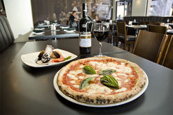 Traditional Neapolitan pizza is the house specialty at stylish Pomo Pizzeria.