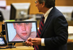 Juan Martinez stands before one of the last pictures taken of Alexander when he was alive.