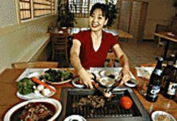 Seoul Garden owner Sarah Kang slices sirloin with a smile.