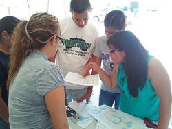 Adriana (right) and other student volunteers look over maps of the Avondale neighborhoods they&#039;re planning to work.