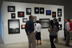 Museum-goers view 100 Suns, a photographic installation that uses documentary imagery from A-bomb testing in the Nevada desert during the 1950s and '60s.