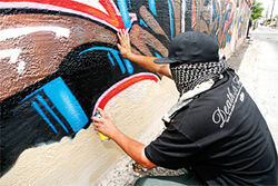 DOSE busts out a graffiti piece in broad daylight.