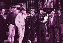 The Gin Blossoms during their 1996 appearance on Saturday Night Live. Rhodes (third from left) with Wilson (center) and host Phil Hartman.