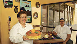 Hope you?re hungry: Chef-owner Rosa Rosas presents the flan de coco while her son Michael sits down with La Bandeja Paisa.