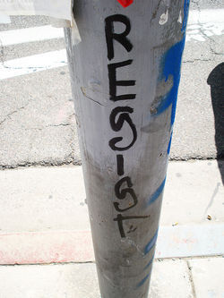 Bobby Castaneda's tagname, RESIST, on a light pole on the corner of Roosevelt and Second streets.