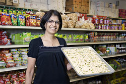 Little India owner Anita Kedia and a tray of her freshly made kalakand dessert.